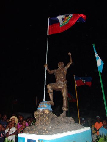 """En la """"Plaza de la Resistencia"""" se alza el monumento de un haitiano que mira el sol sosteniendo en su mano derecha la bandera nacional, alzando su puño izquierdo y pisando un casco azul con la leyenda MINUSTAH Kolera."""